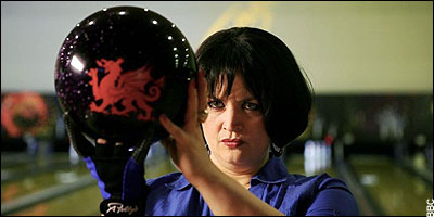 Nessa holding a bowling ball decorated with a Welsh dragon