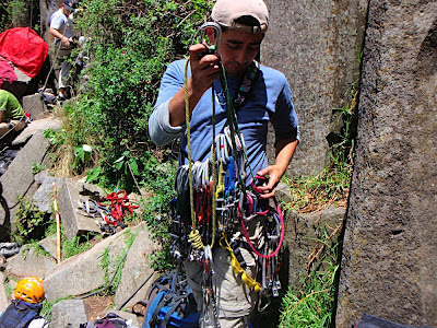 Armando racking up for the climb. Hes going to be lead climbing, so he has to have all gear he needs to put into the wall to protect himself if he falls. basically he has a bunch of cams and stoppers of different sizes. Cams are placed into cracks in the wall and then expand creating an expansion force against the rock and locking into the rock to support you if you fall (hopefully). Stoppers are basically placed where the crack tapers. To me this is really sketchy, but I guess that makes it more fun?
