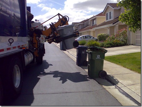 truck lifting the bin with a motorised attachment