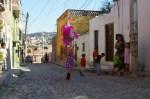 Nadia hitting a Piniata on a cobblestone street of Colonia San Rafael in San Miguel de Allende, Mexico.