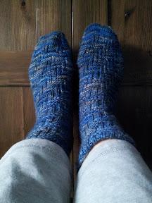 My feet propped against a dark wood wardrobe, wearing blue knitted socks