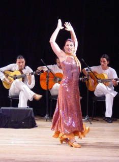 Fernando de la Rua tocando violão à esquerda, Yara Castro bailando ao centro e Conrado Gmeiner com o violão à direita.