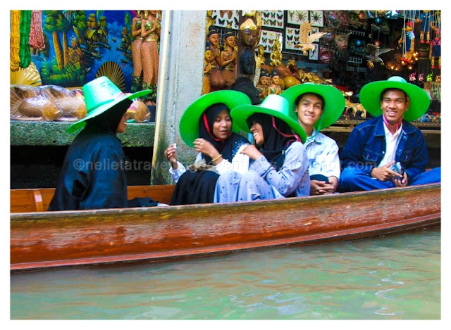 A group of people in the boat as we passed them. They were all wearing bright green hats and were enjoying the time in the floating market of Damnoen Saduak, Thailand.