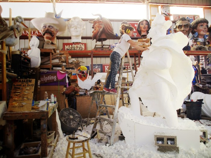 An artist carving a giant block of styrofoam