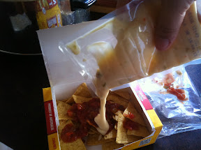 Pouring the cheese on Nachos to Go