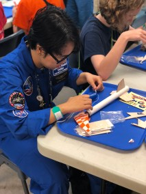 A Space Camp participant builds a rocket using wood and cardboard components.