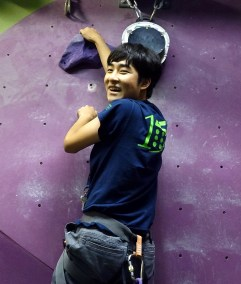 A Sports Camp participant excitedly progresses up an indoor climbing wall.