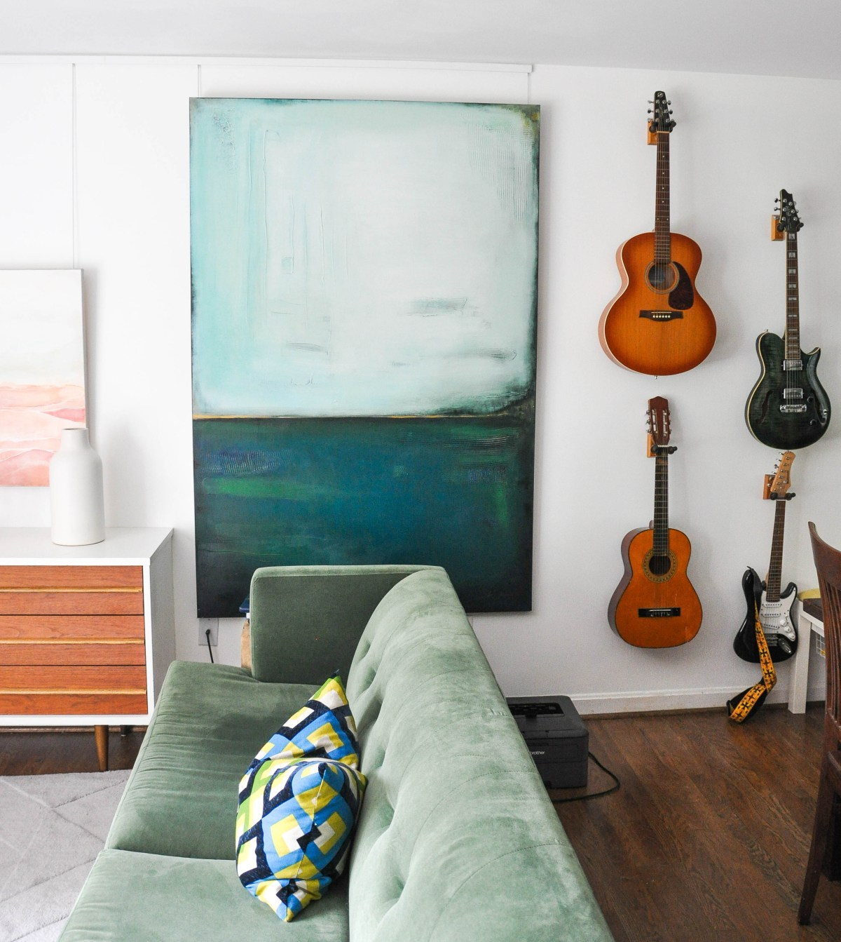 A display of four guitars displayed hanging next to a large abstract painting creates unique wall decor.