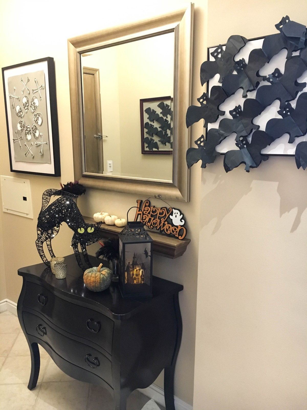 A front hallway entry that has been decorated for Halloween featuring easy Halloween decor and diy wall art.