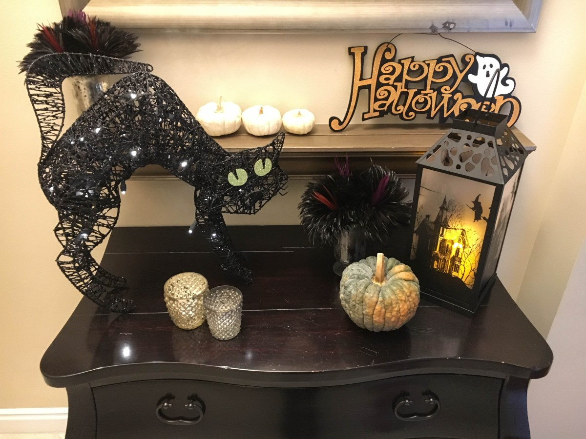 Front entryway table decorated with Halloween decor featuring a light-up black cat, spooky lantern, and mini pumpkins