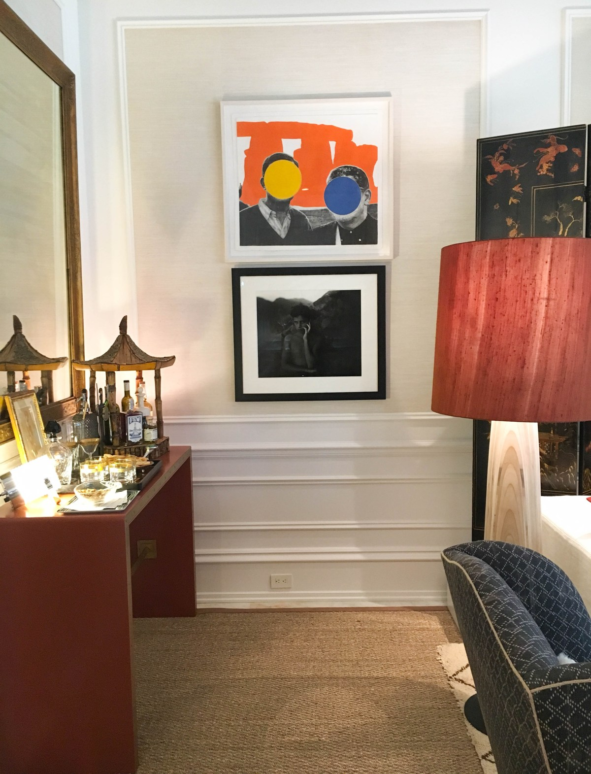 Displayed in the corner of this family room is a cheeky John Baldessari framed print of two gentlemen (standing before an orange stonehenge) whose faces are each hidden by one large colored circle (one yellow and one blue).