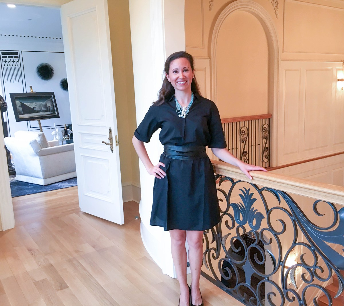 Art consultant Lauren Heller poses in a stylish black dress on the upper level interior balcony of a grand mansion.