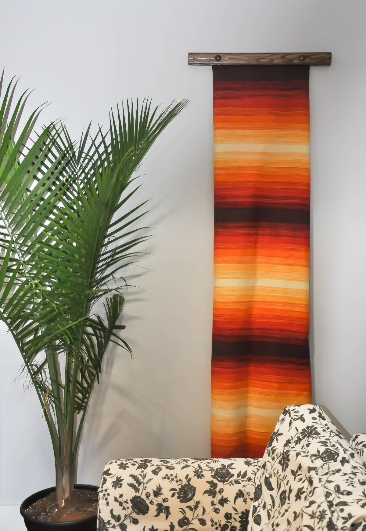 A dark-stained wooden quilt hanger displays a vibrant handwoven textile in a long column in the corner of a living room.