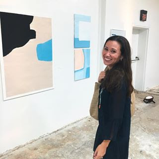 Lauren Heller of Lauren Heller Art Consultant standing before three paintings at a gallery opening turns to smile at the camera.