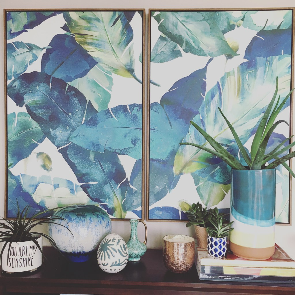 Two framed canvas prints hanging side by side over a bookshelf feature vibrant green and bluish tropical leaves.