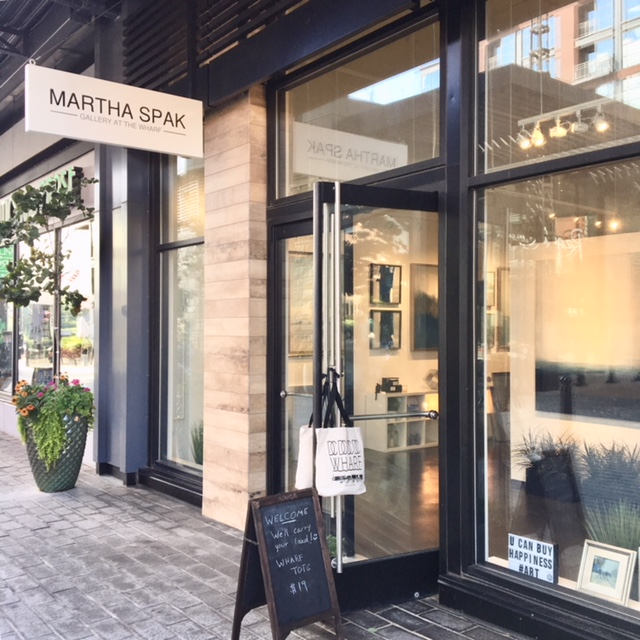 The front entrance to the Martha Spak Gallery features large glass windows through which one can view the paintings on display.