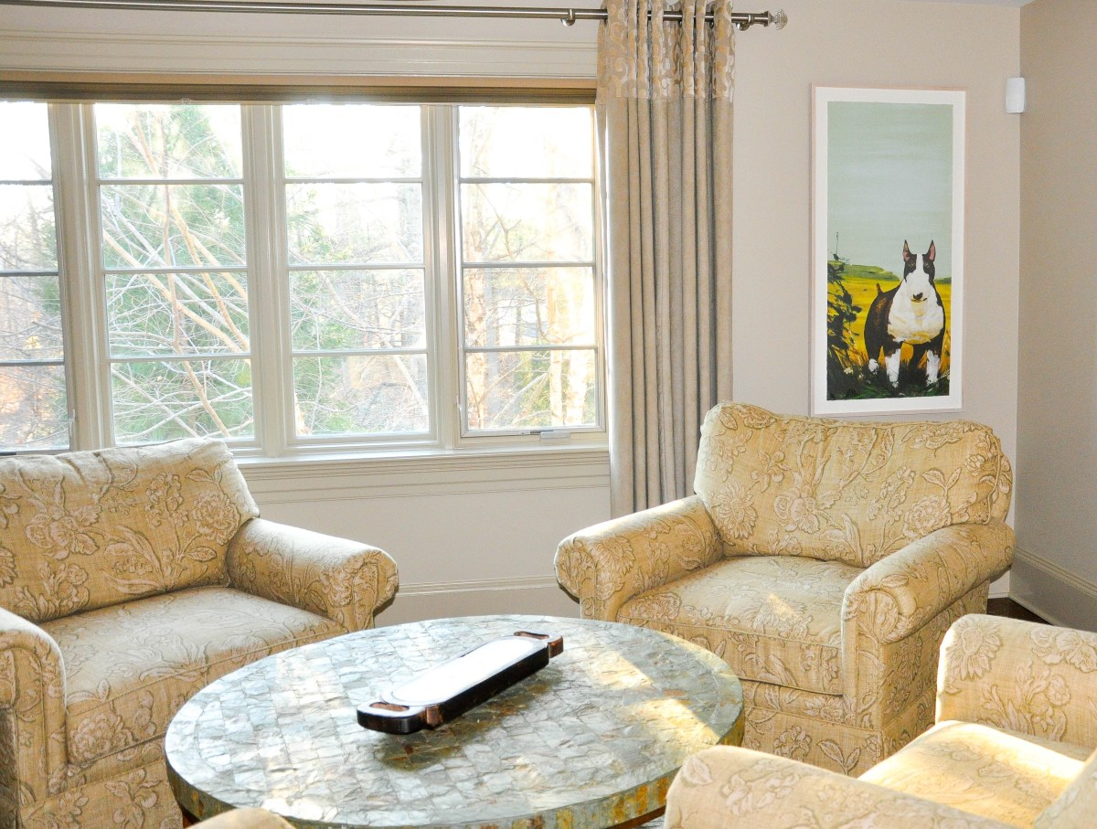 A gorgeous light-filled lounge area showcases a row of large windows and a framed art print of a black and white terrier dog.