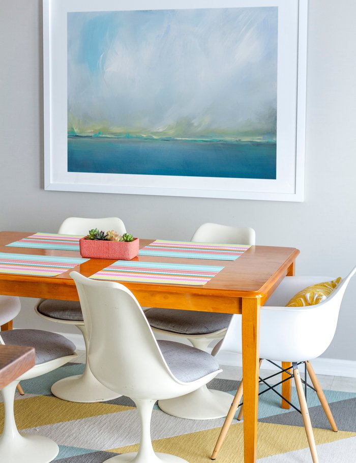 A large abstracted seascape with soft blue hues is displayed in a clean white frame in this relaxed dining area.