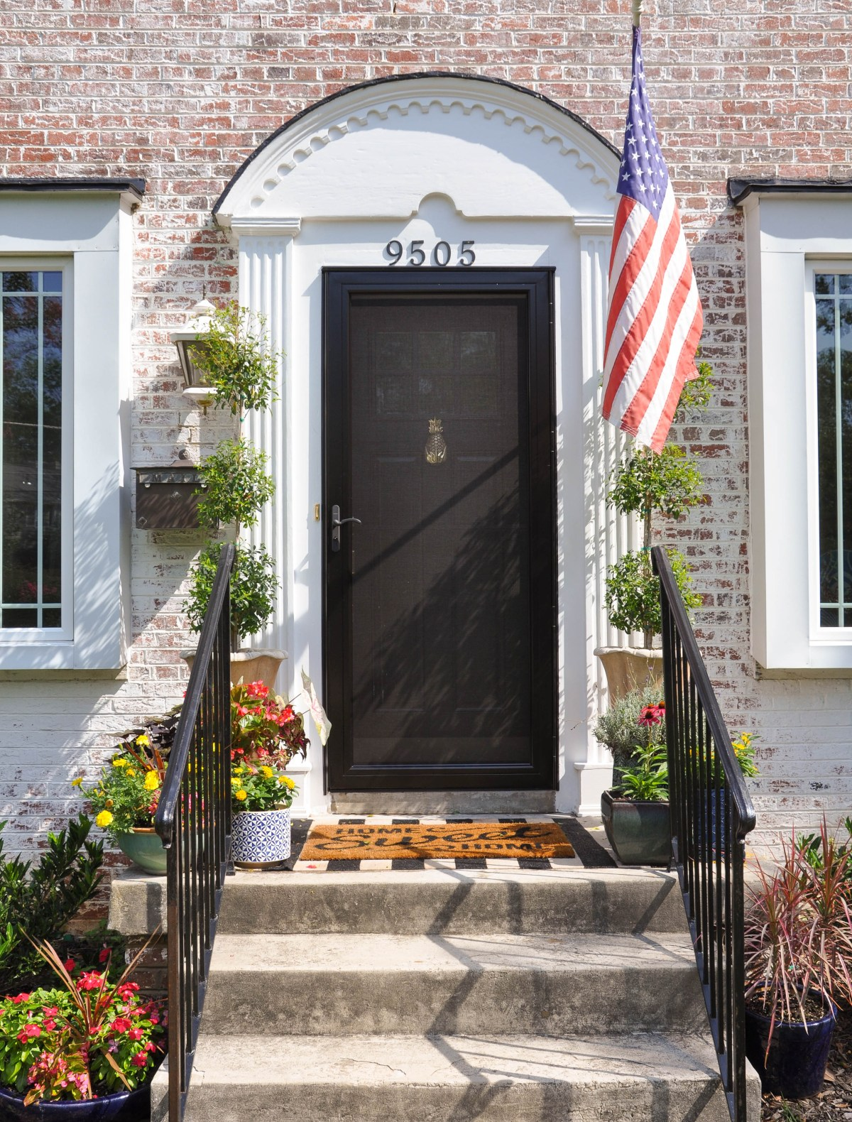 The front entry of a 1940s colonial brick home is brightened by an array of colorful summertime flowers, two layered welcome mats, and a shiny brass door knocker.