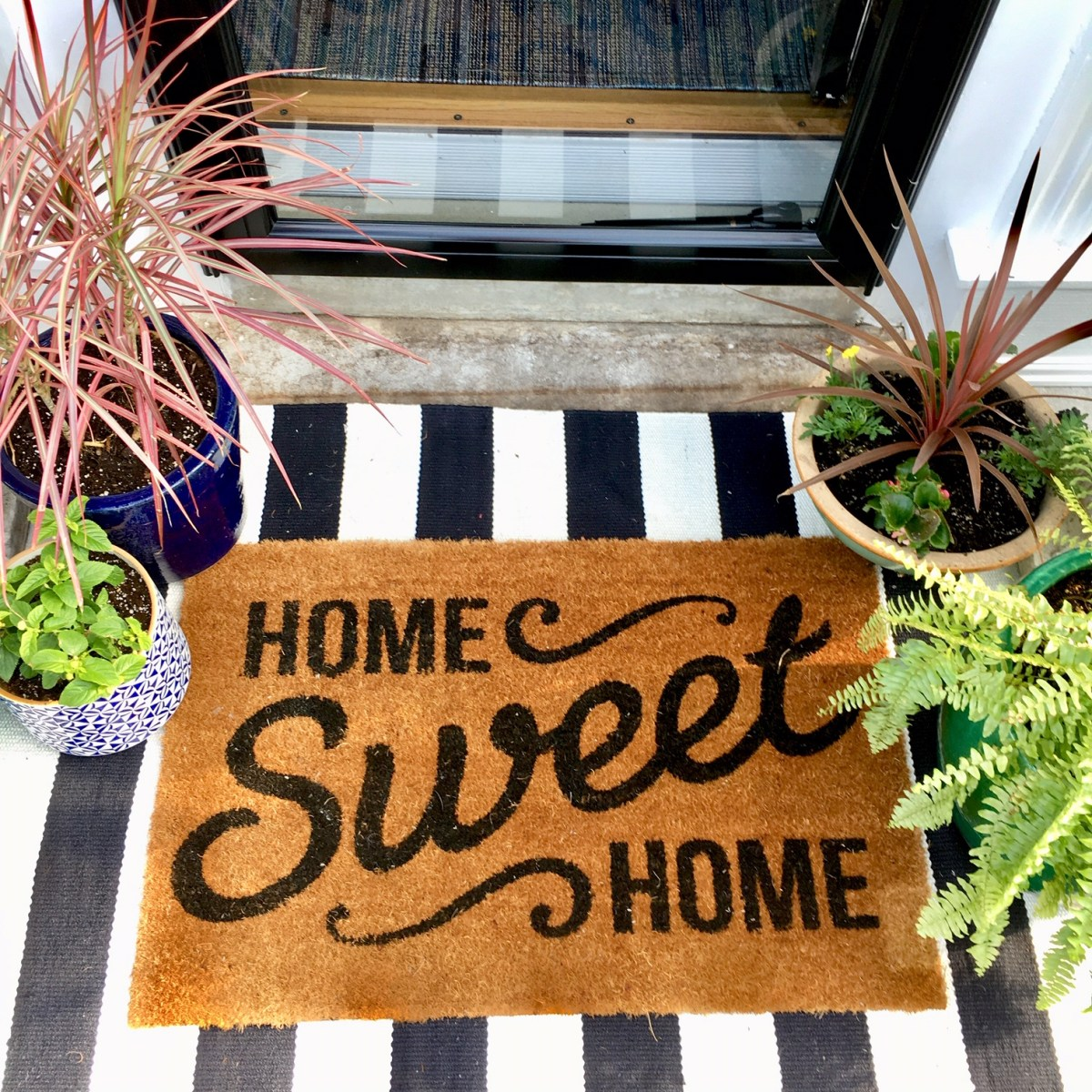 "A cheerful front entry welcomes guests with a doormat that reads, ""Home Sweet Home."""
