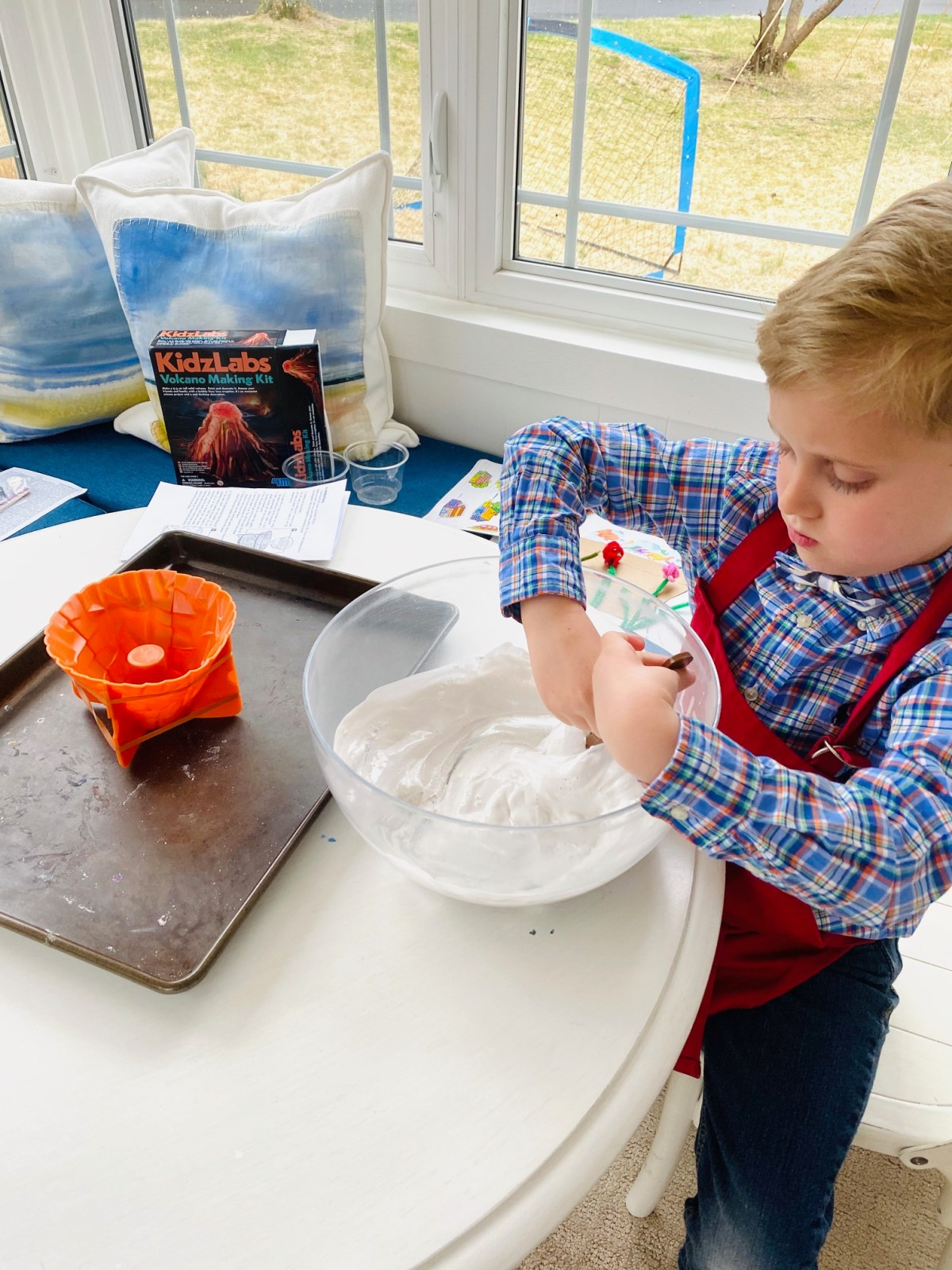 Boy Mixing Plaster in Bowl to Fill Volcano in Kid's Volcano Art Project
