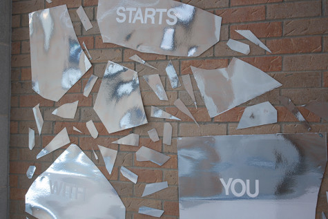 "A part of the IB art mural that says ""It Starts with You"". This part of the mural is reflective."