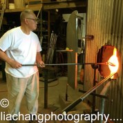 Arlan Huang gathers the molten glass with a hollow steel tube, or blowpipe, gathering the glass from the furnace. Photo by Lia Chang