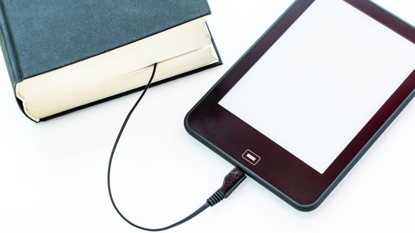 Blue book connected to a mobile device by a cord.