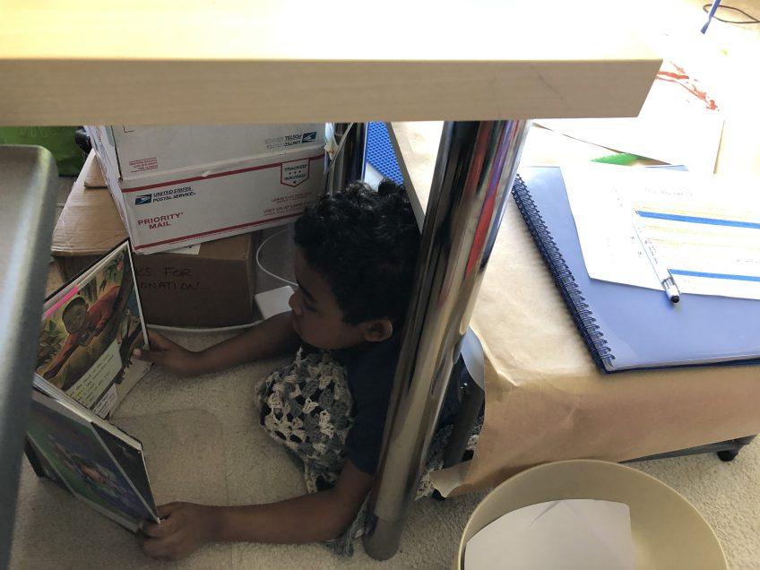 Boy reading underneath a desk.