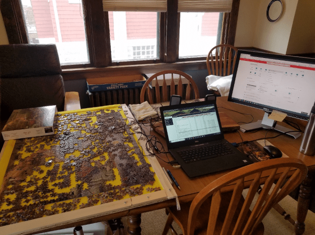 table with puzzle and computer workspace