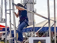Photo of Lydia Howes at the Farm Progress Show demonstrating a safety harness and system designed for those working in grain bins.