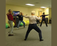 Photo of a group practicing Tai Chi at a Side-by-Side wellness class at the Simmons Cancer Institute.