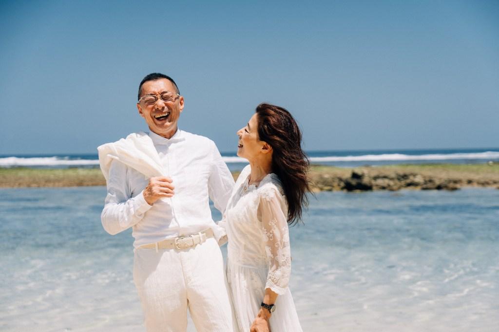 お揃いの白い衣装の年配の夫婦がビーチで笑い合う様子