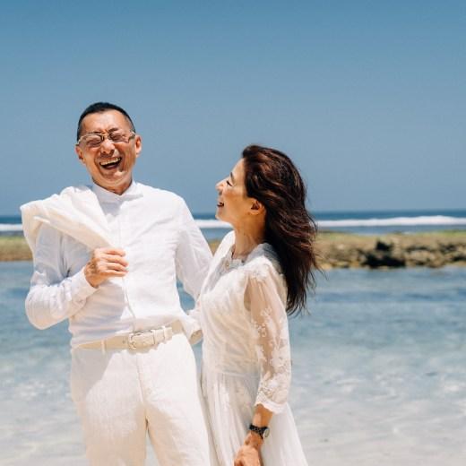 ビーチで笑い合う年配ご夫婦