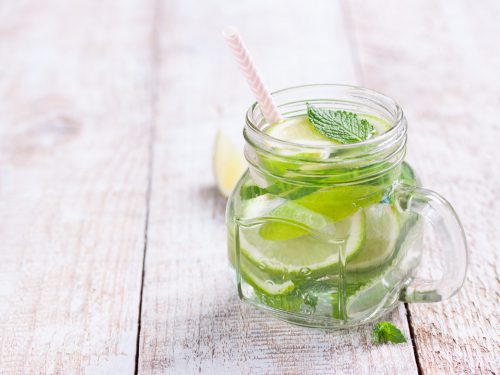 Tasty colorful drink with cold green tea, mint and cucumber in a glass jar on a vintage background, closeup