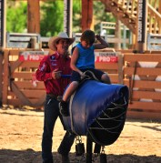 Mike Lee helps a young bull rider at the shriners kiddie rodeo at the Tour Pro Division PBR in Deadwood SD.  Photo by Josh Homer.  Photo credit must be given on all uses.