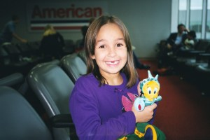 Little girl and Statue of Liberty Tweetie Bird going to New York via American Airlines