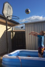T making his own fun - inflatable pool + basketball = awesome!
