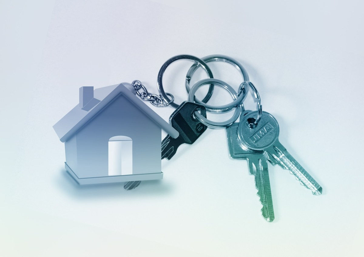 A set of keys, on a key ring, with a house shaped fob, against a plain white background.