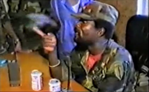 Johnson, shown here in the infamous video, with two cans of Budweiser beer on his desk as he orders his men to torture Doe
