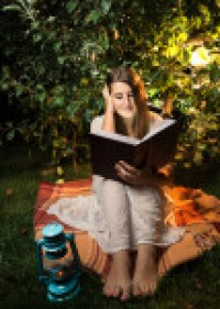 Shot At Night Of Woman Reading Book At Light Of Garden Lantern perhaps Heyer Heroes