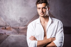 handsome young man with shirt unbuttoned and arms crossed