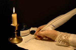 writing with quill pen by candlelight