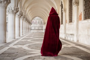 Cloaked woman paces in marble corridor