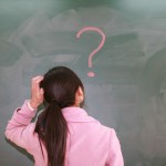 woman gazes at blank wall with question mark