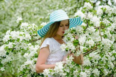 Une femme sentant des fleurs blanches dans un jardin
