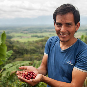 A man smiling and holding coffee berries against a backdrop of a Peruvian landscape
