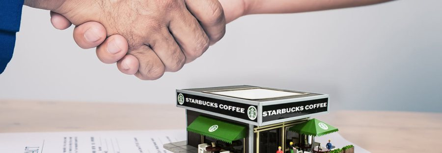 Two people shaking hands over a Starbucks building sitting on real estate contract