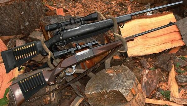 "The rifle on top has a black stock, telescopic sight and is a bolt-action. The one on the bottom is a lever-action, with a scope. Is one a ""sniper"" rifle and the other a ""hunting"" rifle? (Dave Workman photo)"