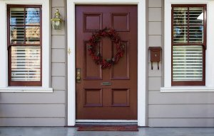 front door that is wooden with two windows and a wreath